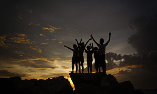 A silhouette of joyful kids by the beach
